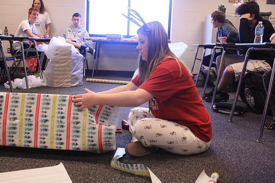 Junior+Tori+Crawford+wraps+a+present+for+Adopt-a-Child+on+Pajama+Day.+