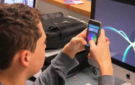 Junior Cameron Hancock plays Trivia Crack during a quiet moment in his yearbook class.